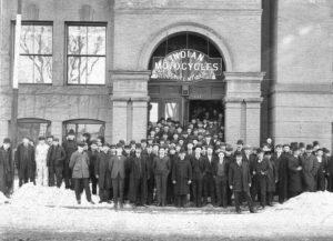 Men standing in front of factory building
